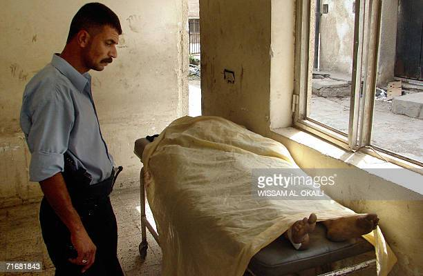 An Iraqi security personnel looks at the body of a Shiite pilgrim 20 August 2006 outside the morgue of a hospital in Baghdad Hundreds of thousands of...