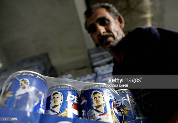 An Iraqi takes Pepsi cans showing the image of football player David Beckham into his shop in Baghdad 03 June 2006 With less than a week for the...