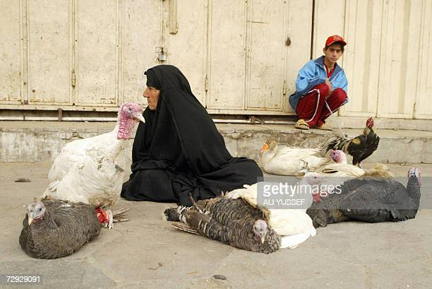 An Iraqi woman and boy wait for customers at the Friday animal market in Baghdad 05 January 2007 US President George W Bush has begun moves to...