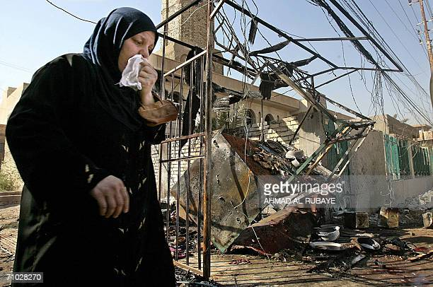 An Iraqi woman passes by a destroyed restaurant 24 May 2006 in Baghdad Eleven Iraqis were killed yesterday evening when a bomb planted in a...