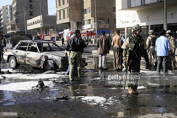 Iraqi police commandos and US soldiers secure the site where a car bomb and a roadside bomb exploded simultaneously in a central Baghdad...