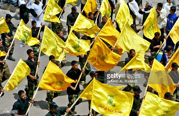 Members of the Shiite Mehdi army militia carry Lebanese Hezbollah flags as they rally at Baghdad's impoverished neighborhood of Sadr City 04 August...