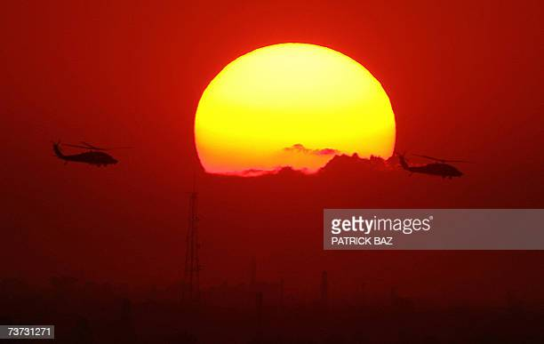 US Army Blackhawk helicopters fly over Baghdad at sunset 28 March 2007 US President George W Bush again warned lawmakers today that he would veto any...