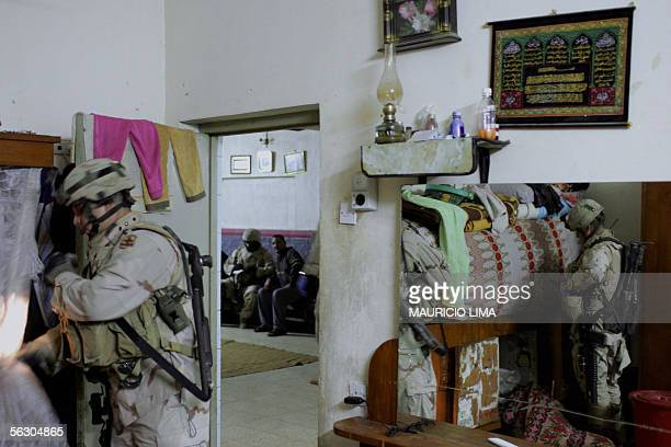 US soldiers from 1st Battalion 184th Infantry Regiment sweep a bedroom as an Iraqi man answers questions to US interpreter in a living room during a...