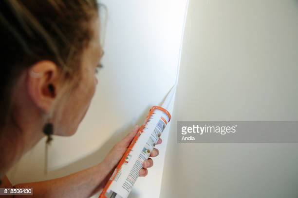 Craftswoman painter interior designor working at a client's place Application of a coating with a paint sprayer