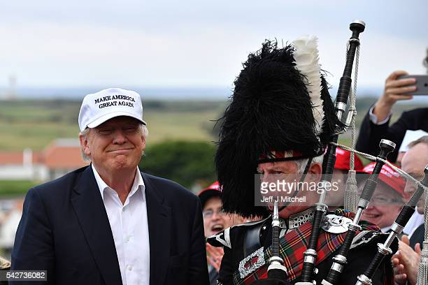 A bagpipe player wears traditional dress next to Presumptive Republican nominee for US president Donald Trump as he arrives to his Trump Turnberry...