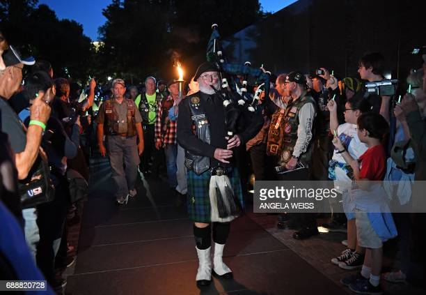 A bagpiper leads a group of Gold Star Mothers who have lost a child in the US military and their supporters during a candlelight vigil near the...