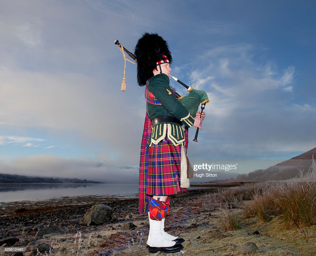 bagpiper playing bagpipes standing next to scottish loch west