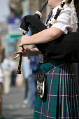Bagpiper playing on sidewalk, mid section