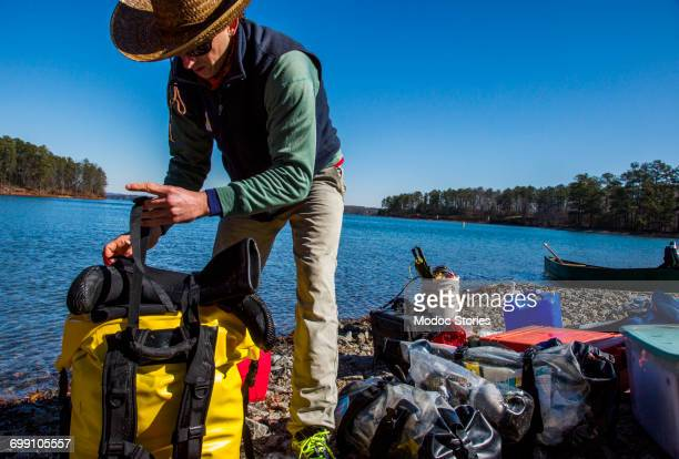 Bags are loaded and carried during the filming of a documentary movie involving a month long journey down the Chattahoochee River from North Georgia to the Gulf of Mexico.