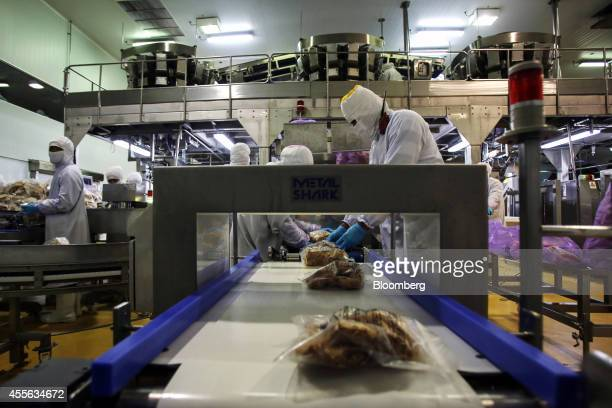 Bags of crumbed chicken pieces move along a conveyor in the packaging section at the Charoen Pokphand Foods Pcl processing plant in Chok Chai Nakhon...
