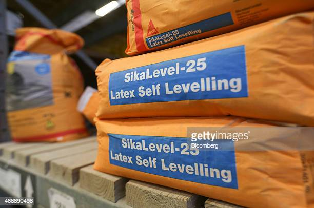 Bags of latex self levelling floor compound manufactured by Sika AG sit for sale inside a BQ home improvement store operated by Kingfisher Plc in...
