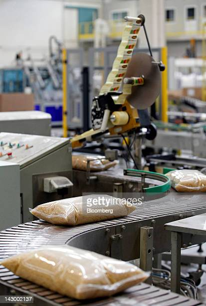 Bags of parboiled rice travel along a conveyor belt at ahead of packaging at Riso Scotti SpA's factory in Pavia Italy on Monday April 2012 The euro...