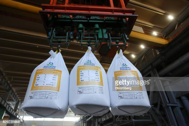 Bags of phosphate plant fertilizer are moved by a mechanical hoist at the PhosAgroCherepovets fertilizer plant operated by PhosAgro PJSC in...