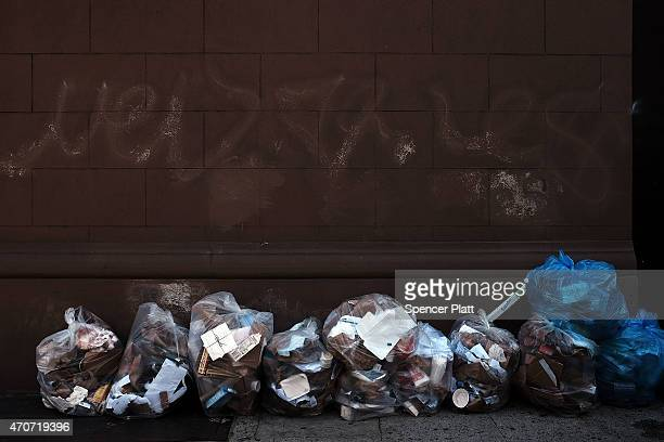 Bags of recycling are piled on a Manhattan street on April 22 2015 in New York City Approximately 19000 tons of metal glass and plastic are collected...