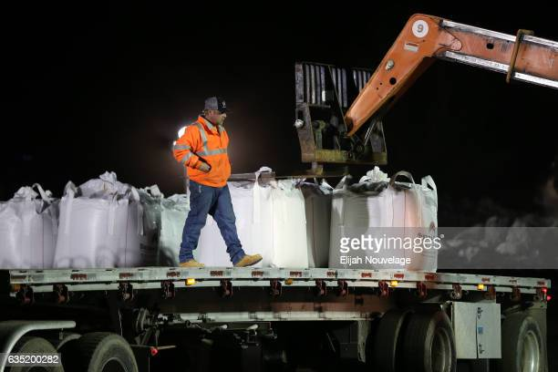 Bags of rocks and sand are unloaded from a flatbed truck as people work through the night to fix the damage below the emergency spillway at Oroville...