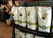 Bags of Starbucks whole coffee beans sit on a shelf as a patron pays for her purchase at a Starbucks store October 3 2006 in Park Ridge Illinois On...