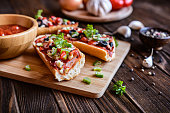 Baguette pizza with bacon, salami, Roquefort cheese, olives, pepper and onion