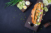 Baguette sandwich with fish, egg, pickled onions and lettuce leaves. Top view