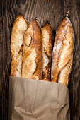 Four baguette bread loaves in paper bag on wooden background