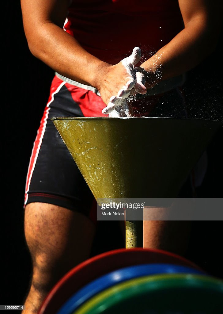 Bagus Danu Saputra of Indonesia chalks up before a lift in the Men's 62kg Weightlifting during day two of the 2013 Australian Youth Olympic Festival at St Ignatius College on January 17, 2013 in Sydney, Australia.