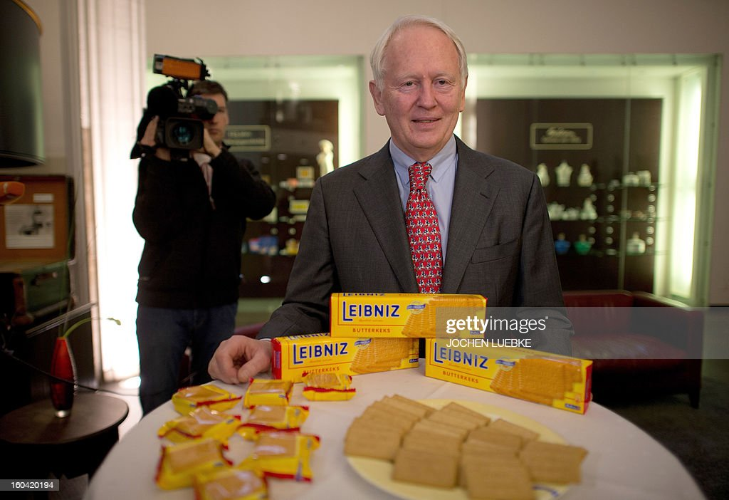 Bahlsen CEO Werner Michael Bahlsen stands on a table displaying Leibniz cookies at the company's headquarters in Hanover, northern Germany, on January 30, 2013. Bahlsen appealed to the extortionists to return the stolen cookie logo. A letter which was sent to a newspaper by the alleged thieves of the logo of the Bahlsen biscuit company by Sesame Street character 'Cookie Monster' claimed responsibility for the theft demanding the company to deliver free cookies to children's hospitals in order to get the trademark sign back. Police, who initially were checking on whether the letter was a hoax, are now investigating a case of attempted blackmail.