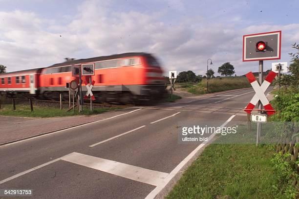 Bahnübergang ohne Schranke in Schulendorf ein Ein D Zug rast mit Tempo 120 km/h durch den Bahnübergang Im Vordergrund Lichtsignal und Andreaskreuz