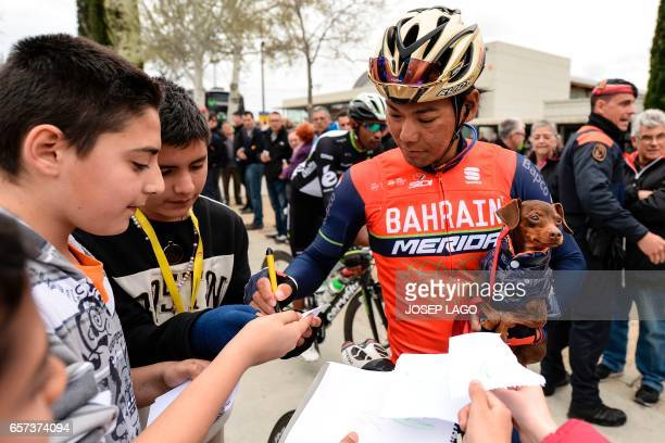 Bahrain Merida's Japanese rider Yukiya Arashiro holds his dog as he signs autographs before the start of the fifth stage of the 97th Volta Catalunya...
