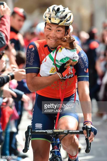 Bahrain Merida's Japanese rider Yukiya Arashiro holds his dog wearing the leader jersey of Volta Catalunya before the start on the sixth stage of the...