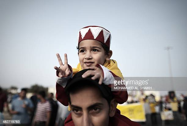 A Bahraini boy carried by his father flashes the sign for victory during a protest against the Formula One Grand Prix and the government in the...