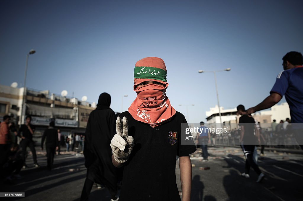 A Bahraini boy flashes the sign of victory in a street following the funeral of a teenager killed in protests marking the second anniversary of a Shiite-led uprising, on February 16, 2013 in the village of Daih, west of Manama. Clashes broke out at the funeral with police using tear gas against mourners, witnesses said.
