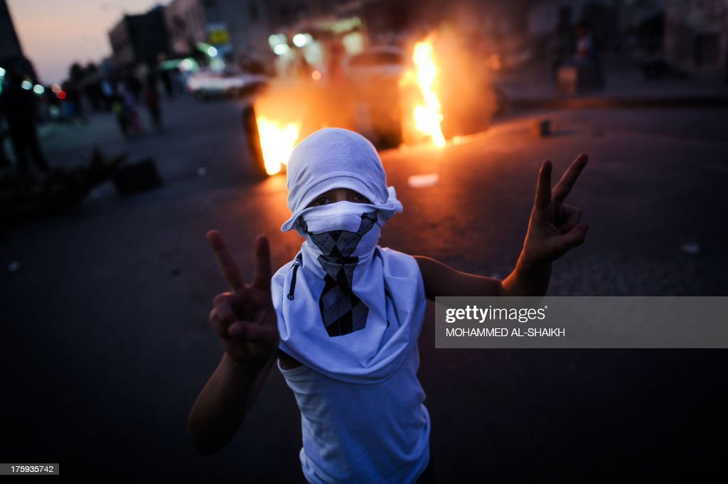 A Bahraini boy flashes the v-sign during the funeral of 10-year-old Ali Jaffer Habib, in the village of Malikiya, on August 10, 2013. Habib, according to his family, died after developing cancer due to the inhalation of tear gas fired by security forces earlier in the year. AFP PHOTO/MOHAMMED AL-SHAIKH