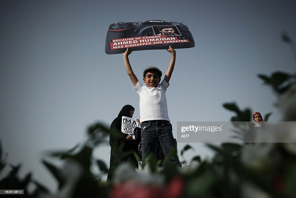 A Bahraini boy holds a placard in the shape of a camera bearing a picture of jailed freelance photographer Ahmed Humaidan during an anti-government protest in the village of Karranah, west of Manama, on March 1, 2013. Humaidan was arrested during a rally on December 29, 2012 and was charged with 'demonstrating illegally' and 'using violence to assault police and damage public properties'.