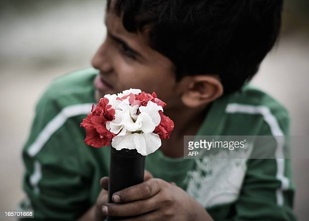 A Bahraini boy holds flowers in an empty tear gas canister that was fired by riot police during a previous demonstration as he takes part an...