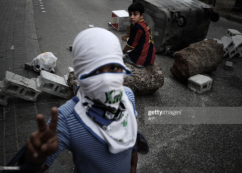 A Bahraini boy makes the victory sign as another sits on a makeshift roadblock placed by protesters during clashes with riot police in the village of Zinj, a suburb of Manama, on March 2, 2013. Protesters were dispersed by police as they tried to reach Salmaniya hospital to retrieve the body of Mahmud al-Jaziri, 20, who succumbed to his wounds on February 21 after he was shot during clashes between police and protesters marking the second anniversary of the February 14, 2011 uprising. His family says Bahraini authorities have not handed over his body because of a dispute over the location of the planned funeral. AFP PHOTO/MOHAMMED AL-SHAIKH