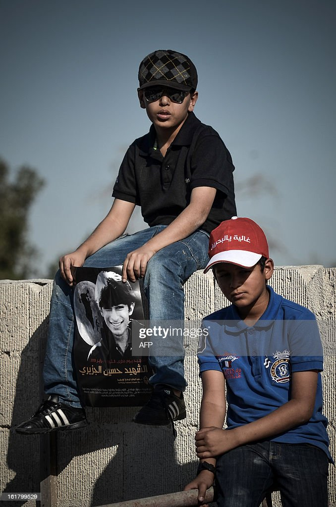 Bahraini childrem mourn during the funeral of Hussain Ali Al Jazeeri (on poster), a teenager killed in protests marking the second anniversary of a Shiite-led uprising, on February 16, 2013 in the village of Jabalat Habshi, west of Manama. Clashes broke out at the funeral with police using tear gas against mourners, witnesses said.