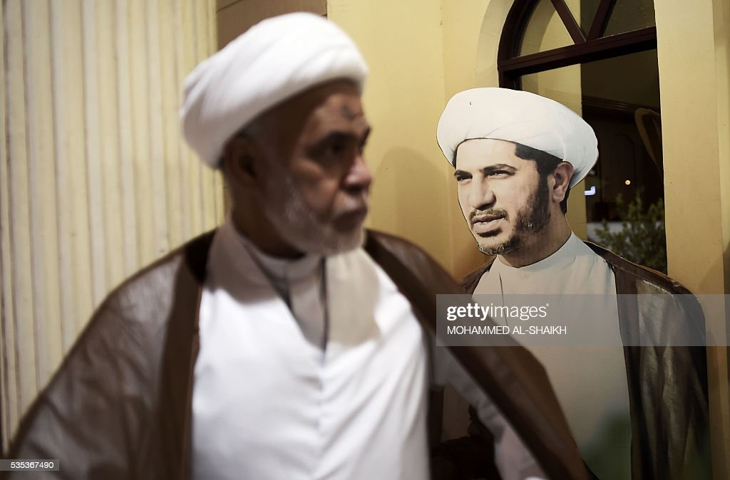 A Bahraini cleric man walks past a placard bearing the portrait of Sheikh Ali Salman, head of the Shiite opposition movement Al-Wefaq, during a protest on May 29, 2016 against his arrest, at Al wefaq headquarter building, in the village of Zinj on the outskirts of the capital Manama. / AFP / MOHAMMED