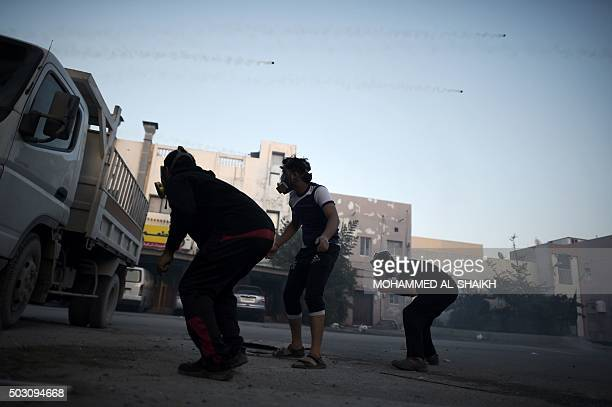 TOPSHOT Bahraini demonstrators duck for cover from teargas fired by security forces during clashes following a demonstration against the government...