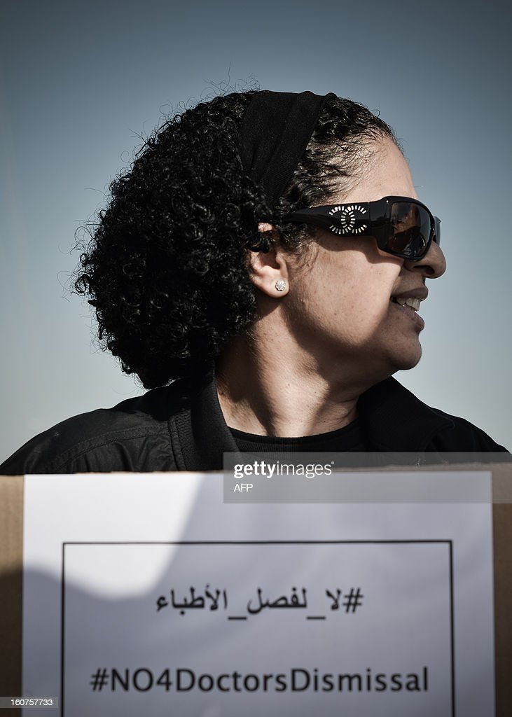 A Bahraini doctor holds a sign against the dismissal of doctors from their jobs because they took part in anti-regime protests during a demonstration outside the labour ministry in Isa, south of the capital Manama, on February 5, 2013. Many Shiite employees were either dismissed or indefinitely suspended from their jobs in the wake of a brutal crackdown on Shiite-led Arab Spring-inspired protests in March 2011.