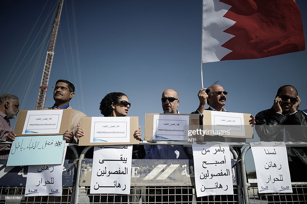 Bahraini doctors hold signs against the dismissal of people from their jobs because they took part in anti-regime protests during a demonstration outside the labour ministry in Isa, south of the capital Manama, on February 5, 2013. Many Shiite employees were either dismissed or indefinitely suspended from their jobs in the wake of a brutal crackdown on Shiite-led Arab Spring-inspired protests in March 2011.