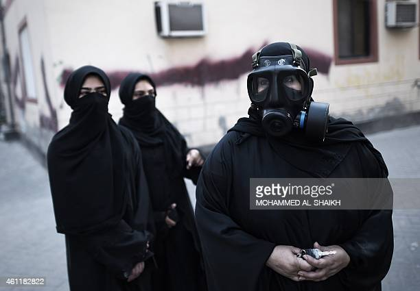 Bahraini female protesters one wearing a gas mask look on during a confrontation with police after a demonstration against the arrest of Sheikh Ali...