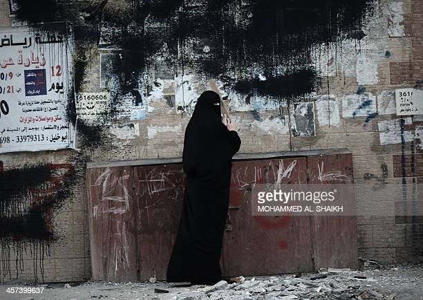A Bahraini female protestor bangs on a box containing gas cylinders as she shouts antigovernment slogans during clashes with security forces...
