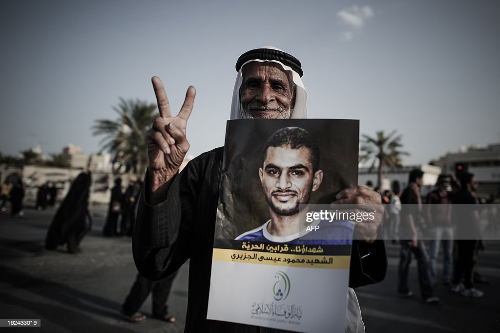Bahraini flashes the sign of victory holding a portrait of Mahmud al-Jaziri, a Shiite protester who died after clashes with Bahraini police, during a demonstration to protest against his death on February 22, 2013 in the village of Daih, West of the capital Manama. Mahmud al-Jaziri, 20, succumbed to his wounds after he was shot during clashes part of the demonstrations commemorating the second anniversary of the February 14, 2011 uprising. AFP PHOTO/MOHAMMED AL-SHAIKH