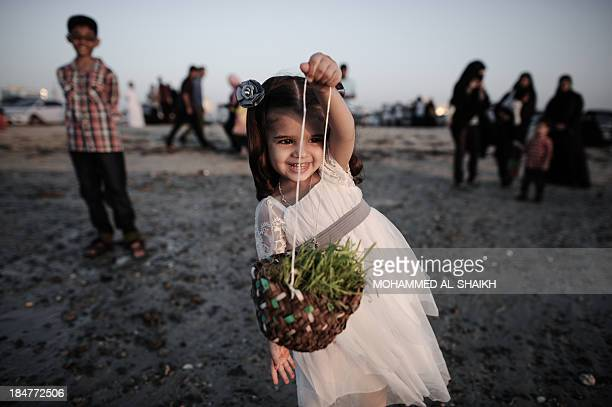 A Bahraini girl holds a basket with Haya Bya plants in the Manama coastal suburb of Karbabad on October 16 2013 The plants are traditionally thrown...