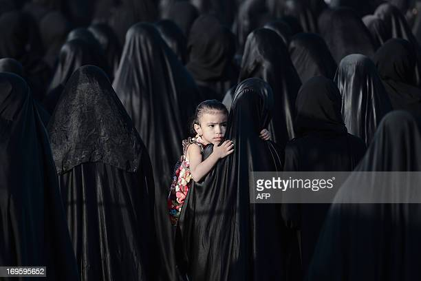 A Bahraini girl is carried by her mother during the funeral of Sayed Omran Sayed Hameed on May 28 in the village of Karzakkan south of Manama Hameed...