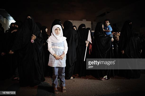 A Bahraini girl stands in front of women taking part in an antigovernment demonstration in the village of Diraz west of Manama late on April 27 2013...