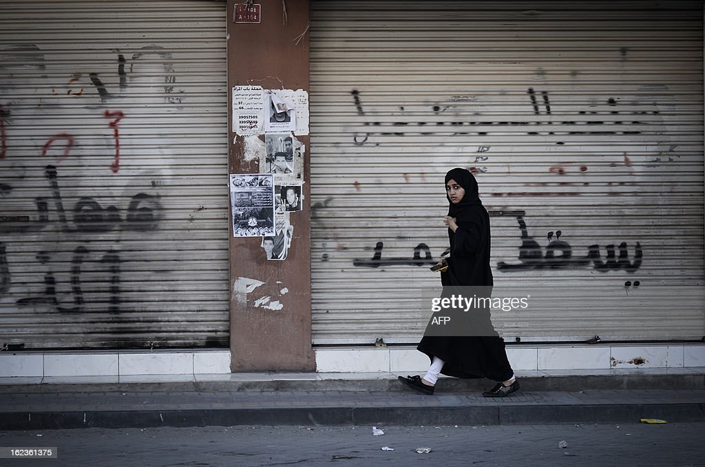 A Bahraini girl walks past closed shutters covered in graffiti as riot police clash with protestors nearby following an anti-regime demonstration against the killing of 20-year old Mahmud al-Jaziri, in the village of Daih, West of Manama, on February 22, 2013. The Shiite protester died of wounds after he was shot during clashes with Bahraini police on the second anniversary of the February 14, 2011 uprising.