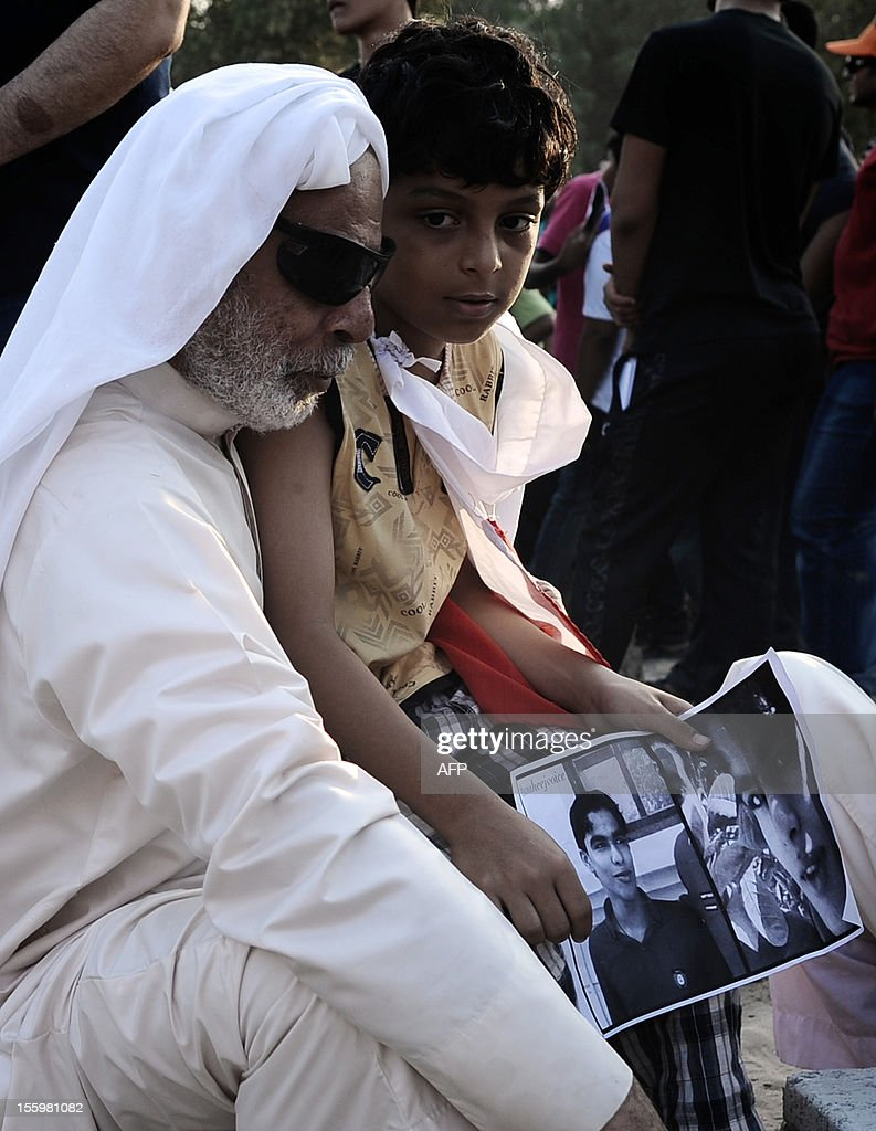 A Bahraini man and a child holding a photograph of 16-year-old Ali Abbas Radhi, attend his funeral in the village of Samahij, Muharraq City, east of capital Manama on November 10, 2012. The Shiite Muslim teenager died after he was knocked down by a car while being chased by Bahraini police during a crackdown on protesters, the opposition said. AFP PHOTO/MOHAMMED AL-SHAIKH