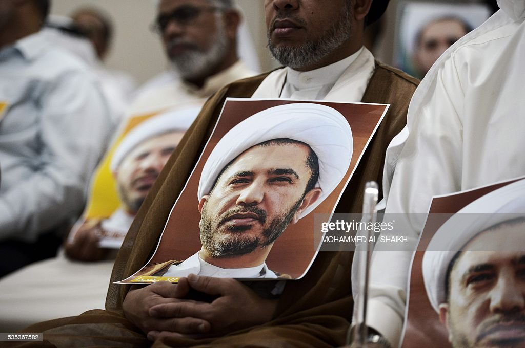 A Bahraini man holds a placard bearing the portrait of Sheikh Ali Salman, head of the Shiite opposition movement Al-Wefaq, during a protest on May 29, 2016 against his arrest, at Al wefaq headquarter building, in the village of Zinj on the outskirts of the capital Manama. / AFP / MOHAMMED
