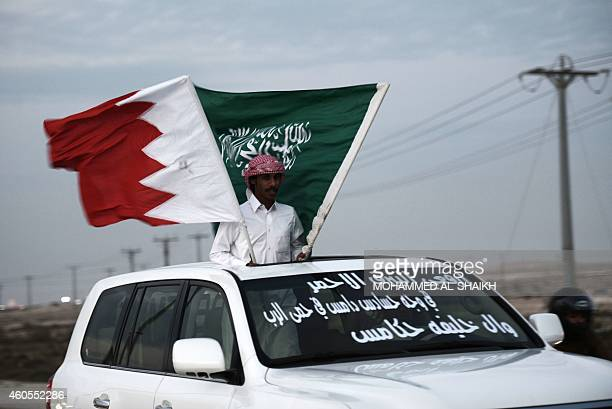 A Bahraini man holds up national flag of Saudi Arabia and Bahrain as Bahraini celebrat the country's National Day in Sakhir south of Manama on...